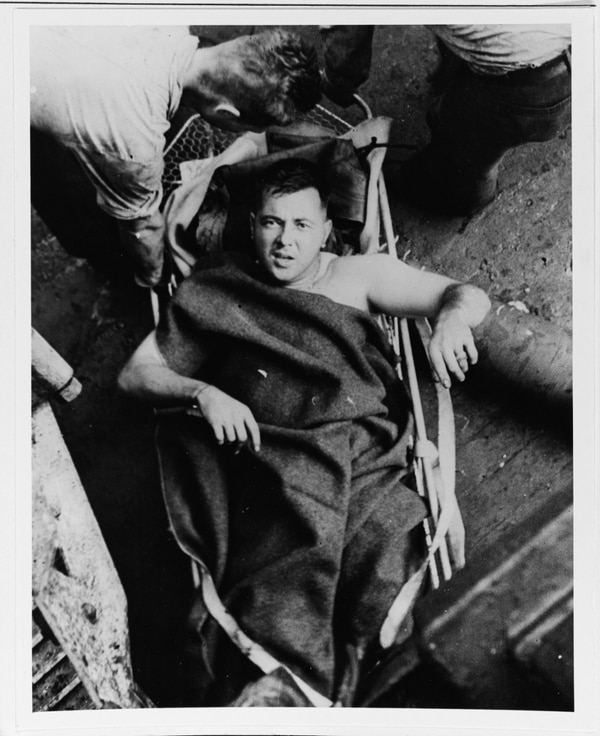 A wounded man in a stretcher on board USS the heavy cruiser Minneapolis on Dec. 1, 1942, the day after the ship was damaged by torpedoes in the Battle of Tassafaronga. (National Archives)