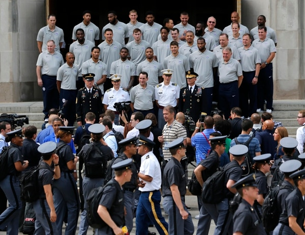 United States basketball head coach Mike Krzyzewski, center, and players on the national team, pose for a photo on the steps of Washington Hall as cadets line up before lunch at the U.S. Military Academy on Monday, Aug. 18, 2014, in West Point, N.Y. The team held an afternoon practice session at the academy. (AP Photo/Mike Groll)