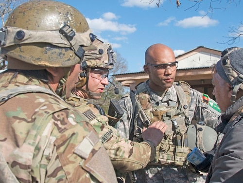 Capt. Kristopher Farrar, an infantryman assigned to 1st Battalion, 1st Security Force Assistance Brigade, center left, communicates to an acting village elder that the Afghan National Army is ready to provide security for the village during training at the Joint Readiness Training Center Jan. 15. (Sgt. Arjenis Nunez/Army)