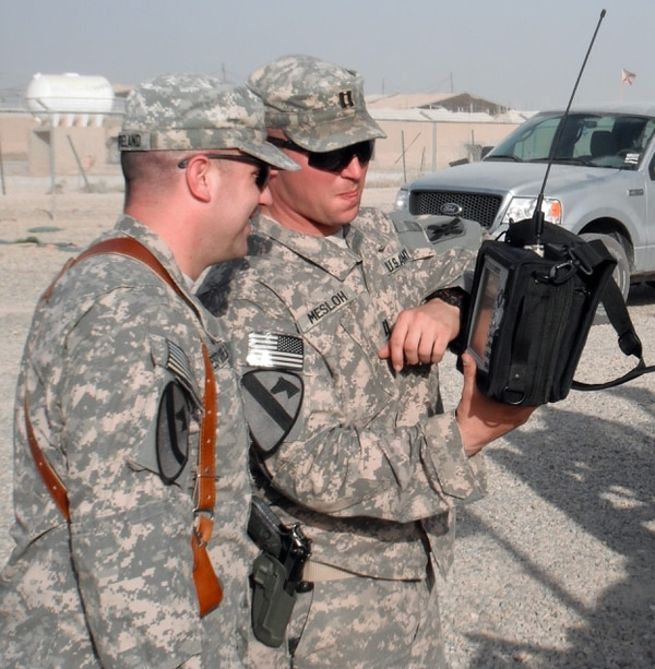 Capt. Thomas Mesloh, electronic warfare officer for the 2nd Squadron, 108th Cavalry Regiment, 224th Sustainment Brigade, 103rd Sustainment Command (Expeditionary), discusses the measurements on a spectrum analyzer with a convoy escort team commander Oct. 16 at Contingency Operating Base Adder, Iraq. (Photo by: Sgt. Alan Smithee)