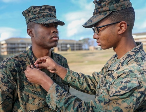 Marine Sgt. Jonathan Foster, a logistics/embarkation specialist, pins Zephrin Green Jr. to the rank of sergeant during a ceremony aboard Camp Lejeune, North Carolina, Jan. 3, 2020. (Cpl. Tawanya Norwood/Marine Corps)