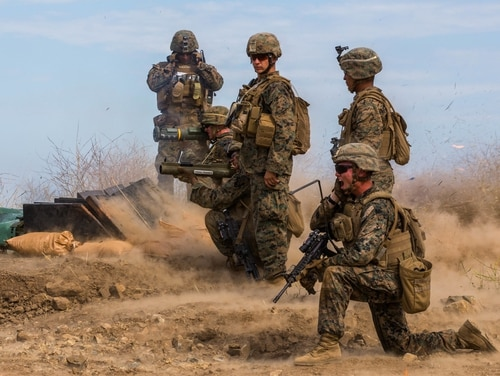 A U.S. Marine, bottom right, with Golf Company, 2nd Battalion, 4th Marine Regiment, 1st Marine Division, calls for rockets to be fired on a target at Range 800, Marine Corps Base Camp Pendleton, Calif. (Sgt. Joshua M. Jackson/Marine Corps)
