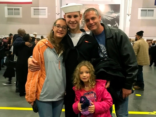 In this Nov. 22, 2019, photo provided by the Walters Family, Cameron Walters, center in Navy uniform, poses for a photo with his sisters, Lily Walters, left, and Shania Walters, right, and his father, Shane Walters, far right, the day he graduated from boot camp in Great Lakes, Ill. (Heather Walters/Courtesy of the Walters Family via AP)