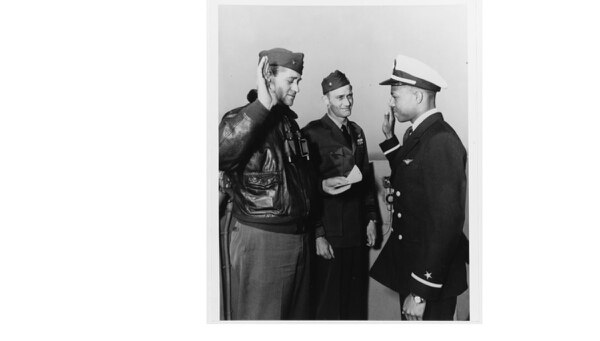 Ensign Jesse L. Brown takes the oath of office on board the aircraft carrier Leyte (CV-32), on April 26, 1949. Administering the oath is the ship's commanding officer, Capt. William L. Erdmann. Lt. Cmdr. E.D. Williams (center) is witnessing the ceremony. (National Archives)