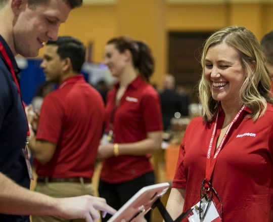 Raytheon and 22 other companies have joined forces to mentor and hire student veterans. Here, Raytheon employees mingle with attendees of the Student Veterans of America national conference. (Raytheon)