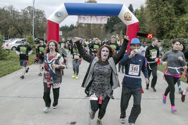 Military families fearlessly kick-off the first ever JBLM Zombie Apocalypse Run here Nov. 1. More than 200 people joined in the scary fun and did their best to survive 100 zombies chasing people throughout the evening.