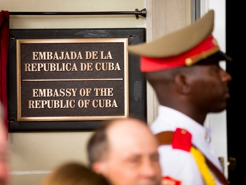FILE - In this july 20, 2015 file photo, a member of the Cuban honor guard stands next to a new plaque at the front door of the newly reopened Cuban embassy in Washington. The State Department has expelled two diplomats from Cuba's Embassy in Washington following a series of unexplained incidents in Cuba that left U.S. officials there with physical symptoms. (Andrew Harnik/AP)