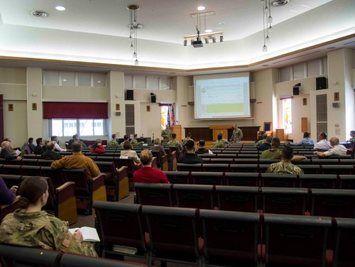 An all-command meeting in Sasebo, Japan, held in a larger space to remain consistent with social distancing practices amid the COVID-19 outbreak. (MC3 Geoffrey P. Barham/Navy)