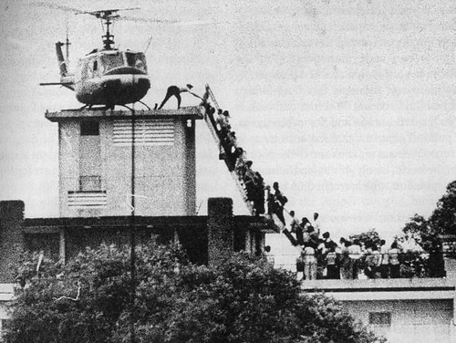 A member of the CIA helps evacuees up a ladder onto an Air America helicopter on the roof of 22 Gia Long Street April 29, 1975, shortly before Saigon fell to advancing North Vietnamese troops.