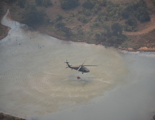 A UH-60 Black Hawk helicopter refills its Bambi Bucket in support of firefighting efforts July 24. (David Larsen/Army)