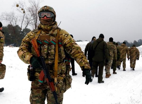 A security officer protects Ukrainian President Petro Poroshenko during military drills on Monday. (Efrem Lukatsky/AP)
