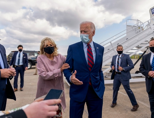 Jill Biden moves her husband, Democratic presidential candidate former Vice President Joe Biden, back from members of the media as he speaks outside his campaign plane in New Castle, Del., on Oct. 5, 2020. (Andrew Harnik/AP)