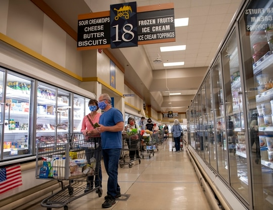 Shoppers wear masks as they wait to pay for their groceries April 16, 2020, inside the commissary at Travis Air Force Base, Calif. (Tech. Sgt. James Hodgman/Air Force)