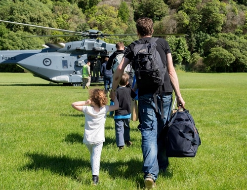 In this image provided by the Royal New Zealand Defense Force, tourists are evacuated by helicopter from Kaikoura following Monday's earthquake, in New Zealand, Tuesday, Nov. 15, 2016. New Zealand military officials said Tuesday that they had evacuated about 140 people by helicopter from a coastal town and were expecting that number to rise to 200 by the end of the day, as a major rescue operation unfolded following a powerful earthquake. (Royal New Zealand Defense Force via AP)