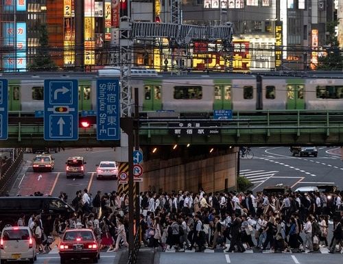 In this June 4 photo, a Yamanote Line train travels above commuters walking across the crossing during evening rush hours in the Shinjuku district of Tokyo. (Jae C. Hong/AP)