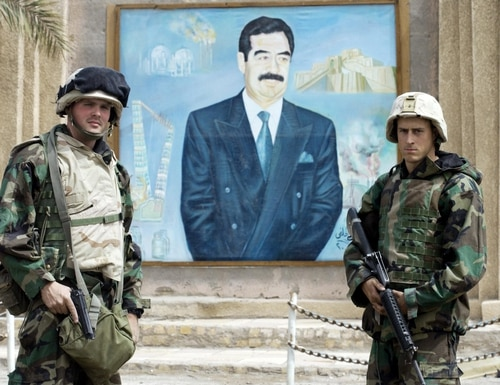 U.S. Marines pose for a souvenir picture in front of a portrait of Iraqi President Saddam Hussein on March 24, 2003, in Nasiriyah. (Eric Feferberg/AFP via Getty Images)