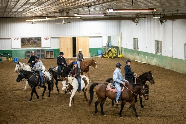 In this Nov. 15, 2018, photo, a group of military veterans, under the direction of Lynn Winkelmann, ride horses in the arena at Wildwood Hills Ranch of Iowa, near St. Charles, Iowa. (Kelsey Kremer/The Des Moines Register via AP)