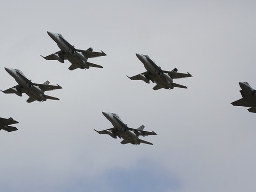 The first F-35 fighters to be permanently based in Australia fly in formation with four RAAF F/A-18A/B Hornets on their arrival.