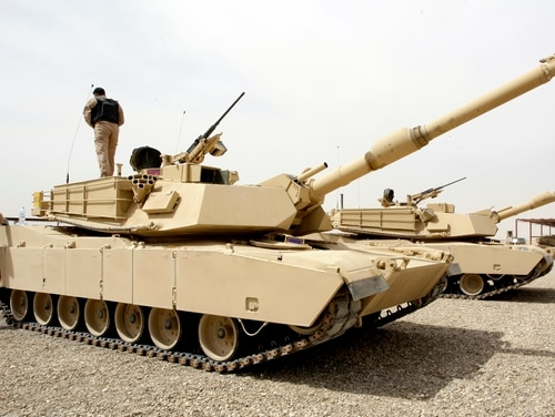An Iraqi soldier stands atop an Abrams M1A1 tank while another jumps to the ground at the joint Iraqi-American military base of Basmaya on March 15, 2010. (Ali Al-Saadi/AFP/Getty)