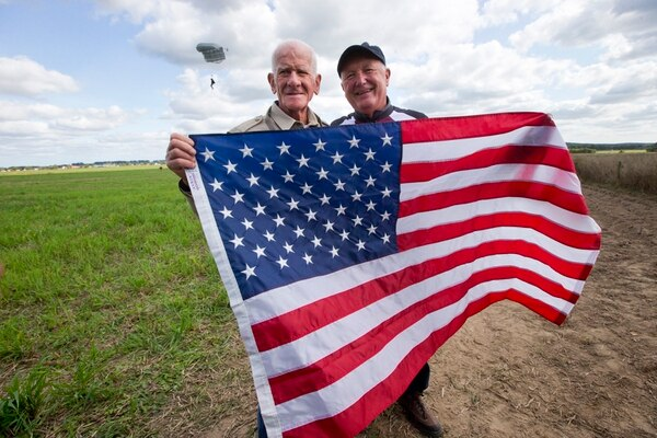 Tom Rice, a 98-year-old American WWII veteran, and U.S. Ambassador Pete Hoekstra, right, pose with the U.S. flag after landing with a tandem parachute jump from a plane near Groesbeek, Netherlands, Thursday, Sept. 19, 2019, as part of commemorations marking the 75th anniversary of Operation Market Garden. (Peter Dejong/AP)