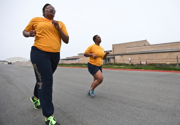Petty Officers Theresa Derby, left, and Lentoyi White run through the morning fog as part of their exercise routine Monday Feb. 29, 2016, in Coronado, Calif. The pair are trying to improve their fitness in order to pass the Navy's fitness test and remain in the Navy. (AP Photo/Lenny Ignelzi)