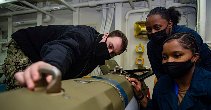 Aviation Ordnanceman Airmen Tristan Comfort, from left, Lashala Jones and Tashley Pierre, adjust a lug on a guided bomb training unit in an ammunition storage room aboard the aircraft carrier Harry S. Truman April 20 during its extended carrier incremental availability at Norfolk Naval Shipyard, Va. (MCSN Tyler Cardoza/Navy)