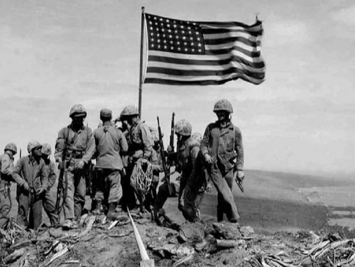 Risking sniper fire, Marines gather around the colors obtained from LST-779 as they snap in the wind at the summit of Mount Suribachi on Feb. 23, 1945. (Pvt. Bob Campbell/Marine Corps/National Archives)