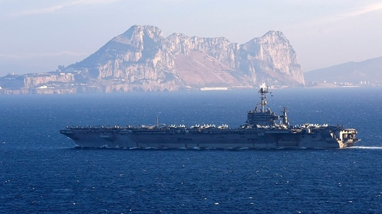 The carrier Harry S. Truman transits the Strait of Gibraltar. Harry S. Truman and her escorts are returning to Norfolk after just three months, a major break from Navy norms. (MC2 Thomas Gooley/Navy)