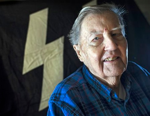 Hugh Montgomery, 91, poses for a photograph with the Nazi SS flag which was flying over Buchenwald concentration camp during WWII, in the background in his McLean, Va., home, Tuesday, Nov. 24, 2015. Montgomery went behind enemy lines for the OSS, where he was among the first Americans to enter the Buchenwald concentration camp. After returning to Harvard to earn his PhD and teach, he joined the newly formed CIA, where he led spying operations against the Soviets for decades, doing tours in Rome, Paris and Moscow. (AP Photo/Cliff Owen)