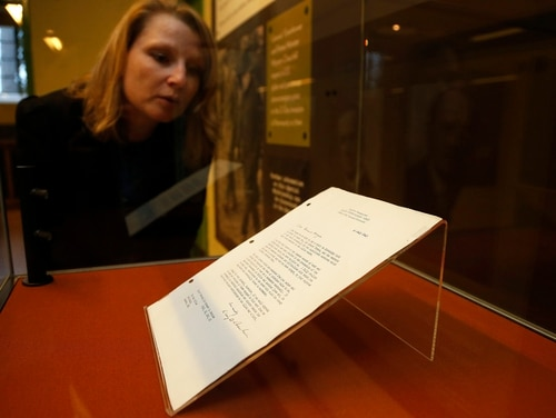 A woman looks at a letter from U.S. President Dwight D Eisenhower as it is put on public display at Bletchley Park in Bletchley, England, Tuesday, March 15, 2016. The secret letter which confirmed the importance of Bletchley Park's World War Two intelligence operation is coming out of the shadows to go on public display for the first time, at Bletchley Park. The personal 'thank you' letter from Dwight D Eisenhower at the end of WWII to Sir Stewart Menzies, wartime chief of the Secret Intelligence Service, spent several years hanging on the wall of the top secret office of the Chief of MI6. (AP Photo/Frank Augstein)