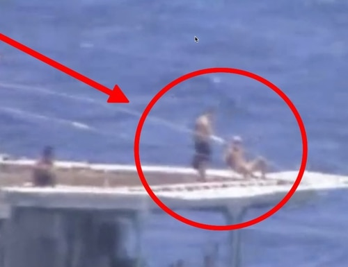 Russian sailors appear to sunbathe on the back of the Russian destroyer