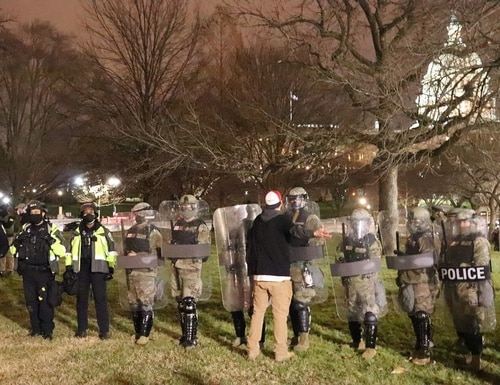 A protester alternating between taunts and pleas, attempting to get the Washington D.C. National Guard to put down their shields and join the the mob on January 6. (Philip Athey)