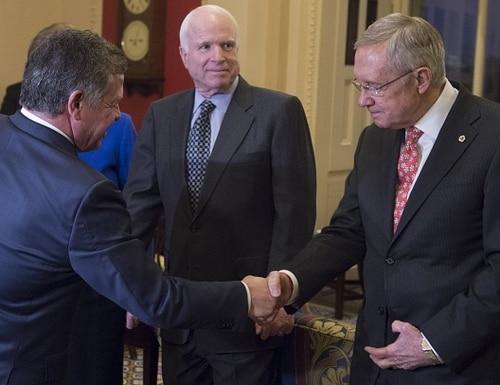 Jordan's King Abdullah II (L) shakes hands with Senate Majority Leader Harry Reid (R) alongside Senator John McCain, Republican of Arizona, prior to a meeting at the US Capitol in Washington, DC, December 2, 2014. AFP PHOTO / Saul LOEB (Photo credit should read SAUL LOEB/AFP/Getty Images)