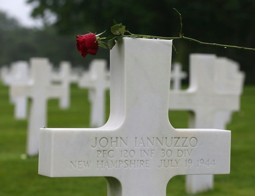 A red rose is placed on the headstone of John Iannuzzo, a 30th Infantry Division soldier killed in action in 1944. His headstone remains at the Normandy American Cemetery and Memorial in France. (David Vincent/AP)