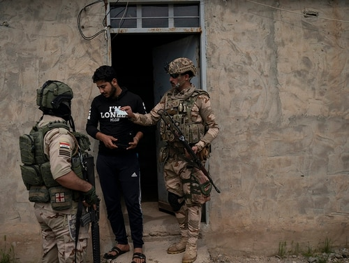 In this April 5, 2019, photo, Iraqi army 20th division soldiers check the ID of a man during a raid in Badoush, Iraq. (Felipe Dana/AP)