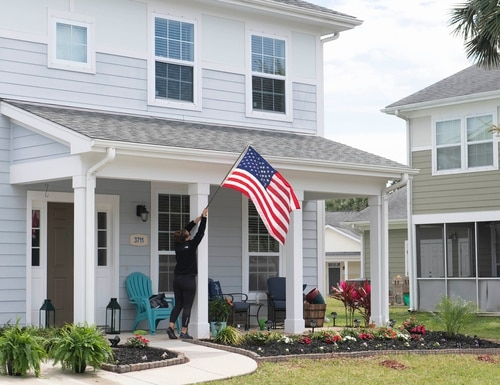 Crista Gyates raises the American flag at her home March 19, 2019, at on-base military housing at Naval Station Mayport. (MC2 Devin Bowser/Navy)