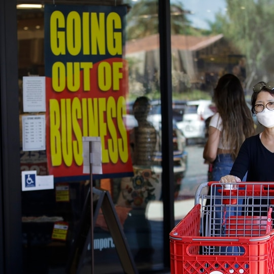 A shopper walks past a Pier 1 Imports store as going out of business signs are posted amid the coronavirus pandemic Wednesday, July 1, 2020, in Santa Clarita, Calif. (AP Photo/Marcio Jose Sanchez)