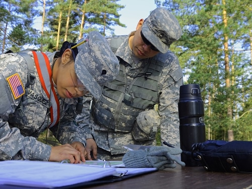 An instructor at the 7th Army NCO Academy helps a Warrior Leader Course student with her land navigation training at the academy's training area in Grafenwoehr, Germany. (Photo by Clifford Kyle Jones / NCO Journal)