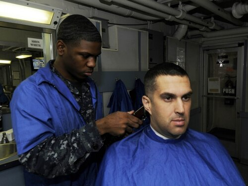 Chief Aviation Electronics Technician Kirk P. Killian, shown here getting a haircut in 2010, pleaded guilty to a charge of wrongful appropriation of military gear on July 29 and was bumped down to E-6. (Navy)