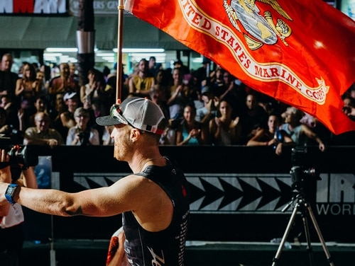 Marine veteran and commentary author Mike Ergo holds the Marine Corps flag at the Kona triathlon Ironman world championship, where he was sponsored to compete. He carried the flag to honor of his fallen brothers, lost to combat and suicide, during the entire marathon section of the triathlon.
