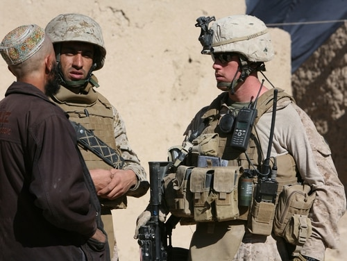 With the help of an interpreter, Cpl. Devon Sanderfield, a squad leader with Lima Company, 3rd Battalion, 4th Marine Regiment, speaks with a villager in the town of Changwalok, Afghanistan. (Cpl. Zachary Nola, Marine Corps).