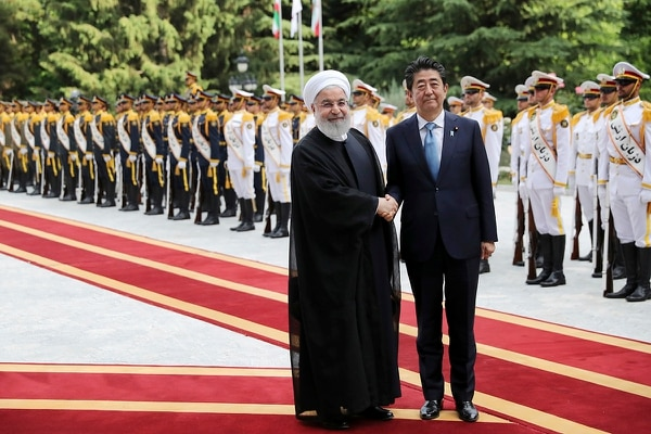 Japanese Prime Minister Shinzo Abe, center, shakes hands for the cameras with Iranian President Hassan Rouhani at the Saadabad Palace in Tehran, Iran, Wednesday, June 12, 2019. (Ebrahim Noroozi/AP)