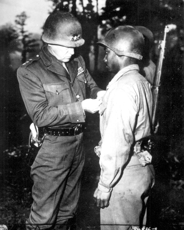Lt. Gen. George S. Patton, U.S. Third Army commander, pins the Silver Star on Pvt. Ernest A. Jenkins of New York City on Oct. 13, 1944, for his conspicuous gallantry in the liberation of Chateaudun, France. (National Archives)