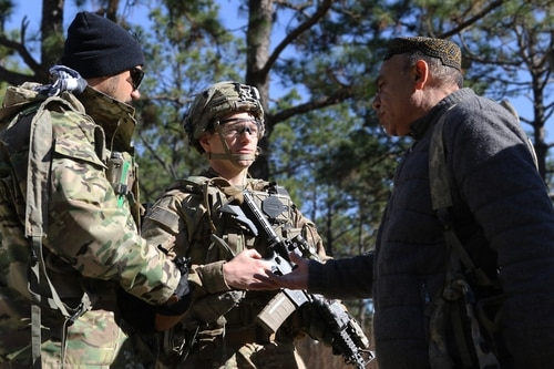 Capt. Justin Alexander, a combat team adviser and leader with the 1st Security Force Assistance Brigade, talks to Afghan National Defense Security Forces role players during training at the Joint Readiness Training Center at Fort Polk, La., in January. (Pfc. Zoe Garbarino/Army)
