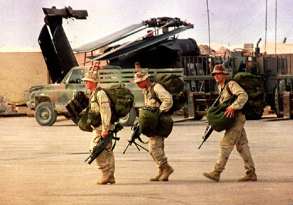 Three homeward bound U.S. Army Rangers carry their bags and M-16 rifles toward a military transport plane at Mogadishu International airport Oct. 21, 1993, for the withdrawal from Somalia. (Hocine Zaourar/AFP via Getty Images)