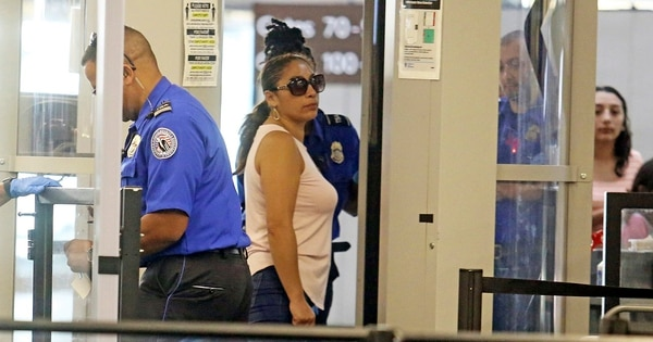 Alejandra Juarez, 38, center, passes through TSA screening at the Orlando International Airport on Friday, Aug. 3, 2018 in Orlando, Fla. Juarez, the wife of a former Marine, is preparing to self-deport to Mexico in a move that would split up their family. Juarez and her husband, former Marine Sgt. Temo Juarez, a naturalized citizen, have raised two daughters, ages 16 and 9, and now Alejandra is headed to Mexico. (Red Huber/Orlando Sentinel via AP)
