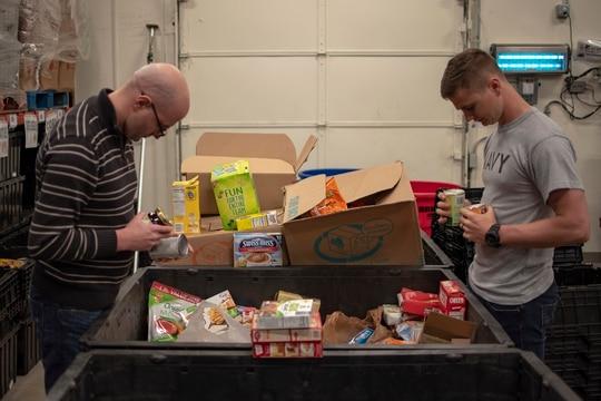 Sailors sort donated food items at a Maryland food bank. (MC2 William Sykes/Navy)
