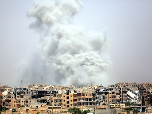 Smoke billows out from Raqqa following a coalition air strike on July 28, 2017. (Delil Souleiman/AFP/Getty Images)