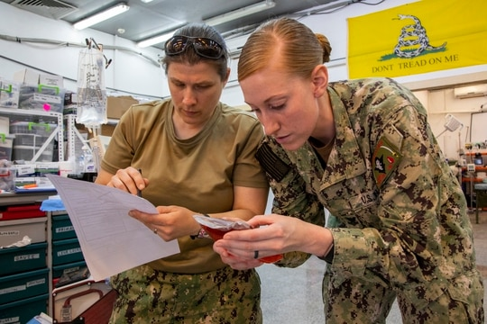 U.S. Navy Lt. Lisa Talledo, left, an emergency/trauma nurse, verifies the serial numbers on a pint of fake blood with U.S. Navy Petty Officer 2nd Class Jamie Hopkins, a pharmacy technician, during a mass casualty training exercise at Erbil Air Base in the Kurdistan Region of Iraq, March 12, 2020. (Spc. Angel Ruszkiewicz/Army)