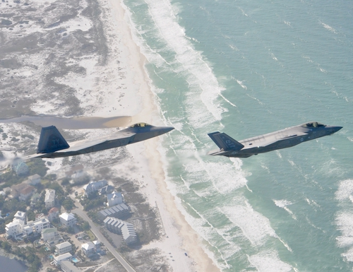An F-22 Raptor from the 325th Fighter Wing flies alongside a F-35 Lightning II from the 33rd Fighter Wing over the Florida Panhandle's Emerald Coast. Tyndall Air Force Base, Fla., will receive three F-35A squadrons starting in 2023. (1st Lt. Savanah Bray/Air Force)